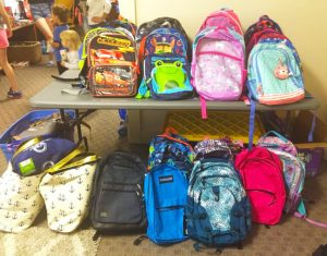 IMG of backpacks filled with school supplies.